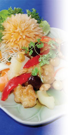 Photograph showing stir fried chicken with pineapple, spring onion, mushroom, water chestnut, cashew nut and lotus seeds, topped with tamarind sauce.